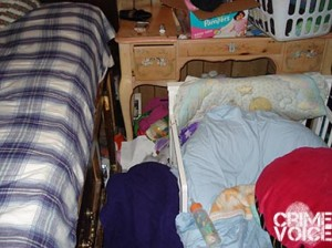 The child's crib placed next to the bed. Coin purse, cigarettes and lighter next to the Pampers on the dresser.