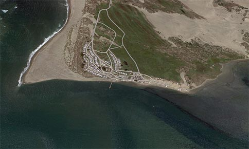 A satellite view of Dillon Beach at Tomales Bay. The white shapes are RV's camping.
