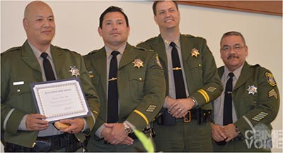 Sheriff's Detective Kevin Mah receives his award with his colleagues