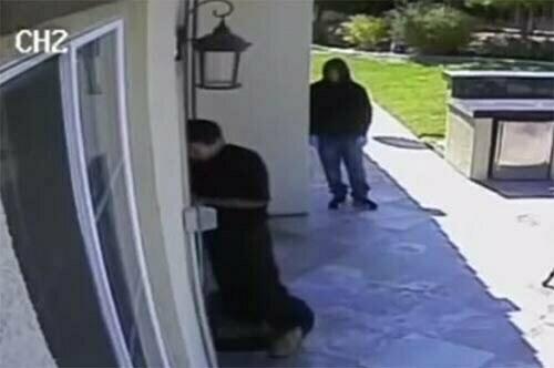 Moses Herrera checks the door while Alvaro Vadivia looks on.
