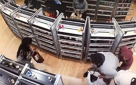 The thieves grab items off the shelves and stuff them into shopping bags (YouTube/Officer Manfredi)
