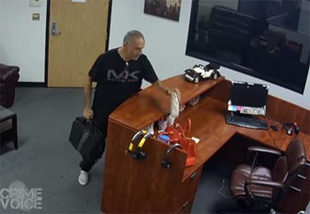 In this shot from earlier in the video, the man is reaching over the desk to take a woman's purse while the room is empty.