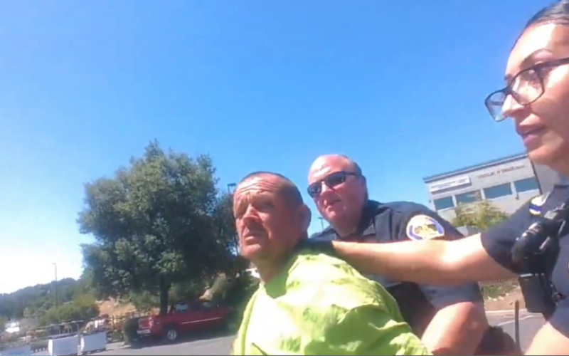Lying down in a planter box, not wanting to be arrested