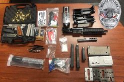 Two gang members arrested as they stand in a garage with guns